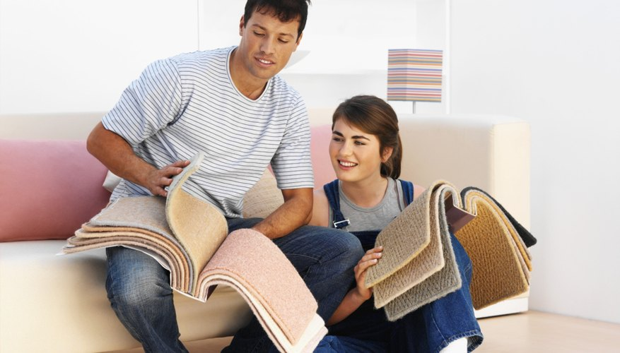 A young couple looking through carpet samples.