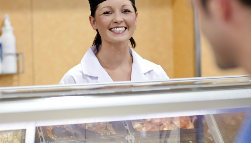 Cheerful female baker listening to a student in the queue of the cafeteria