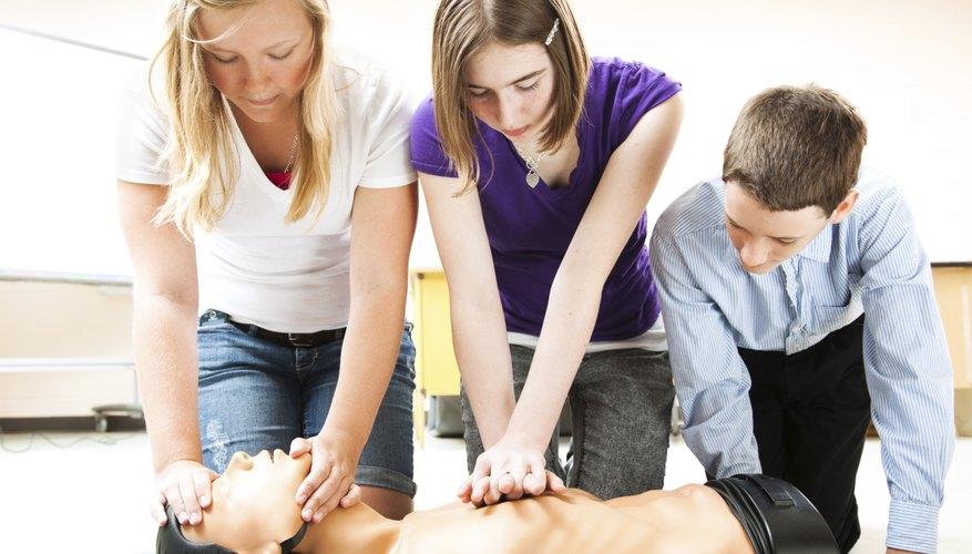 Children performing CPR on dummy