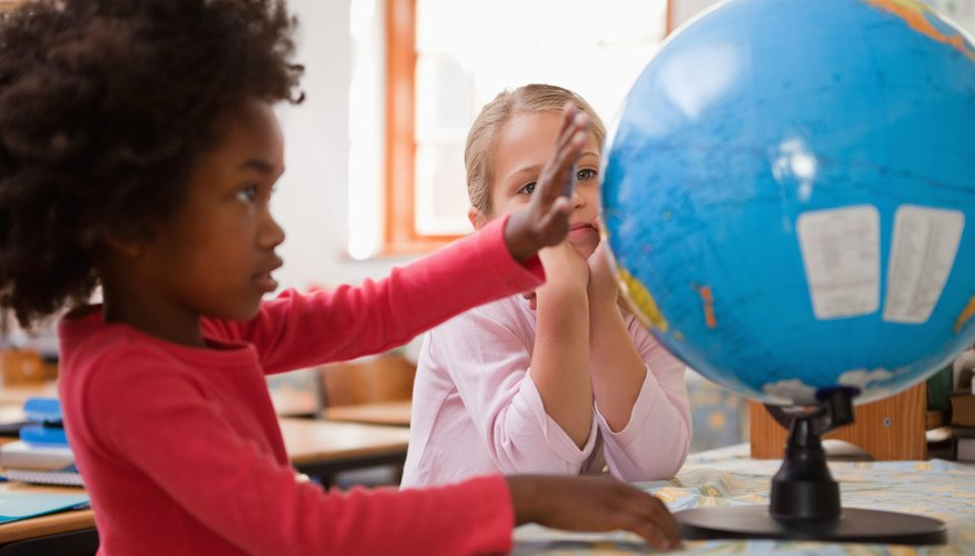 Two students looking at a globe on a table in the classroom.