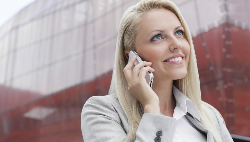 Close-up of smiling businesswoman conversing on cell phone against office building