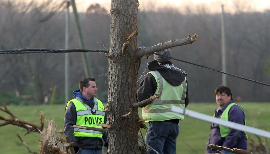 Police officers deal with live electrical wires due to a tornado.