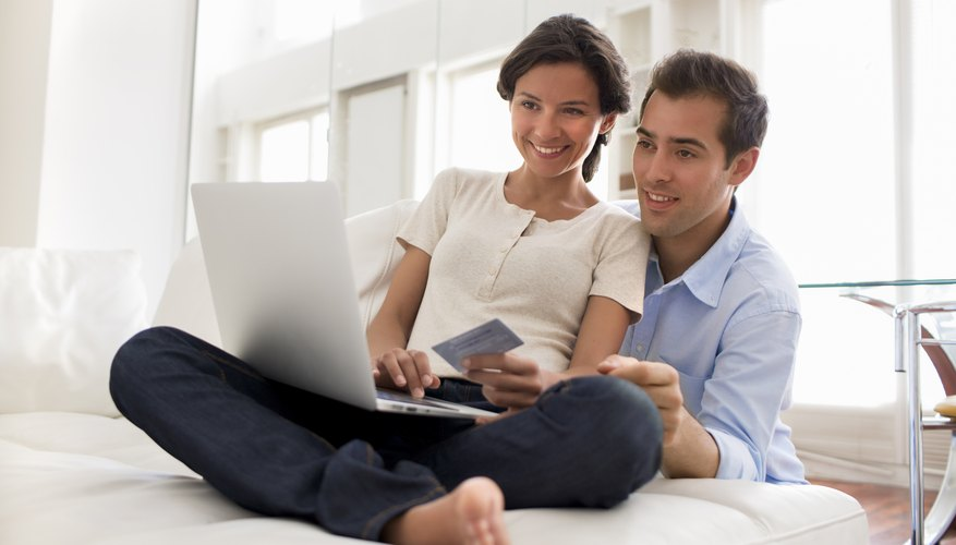 A pair of newlyweds on the couch with a laptop computer and a credit card.
