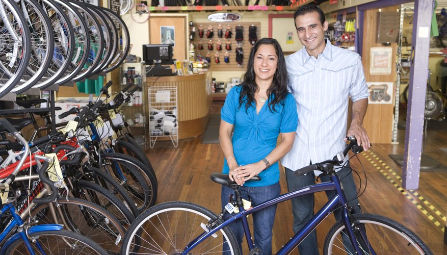 Proud business owners standing with bicycle in bike shop