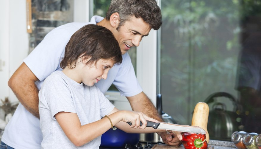 Father teaching child how to slice healthy red pepper