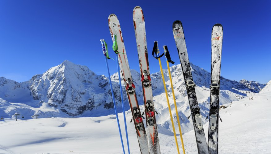 Two sets of skis and pistes stand up in the snow at a resort.
