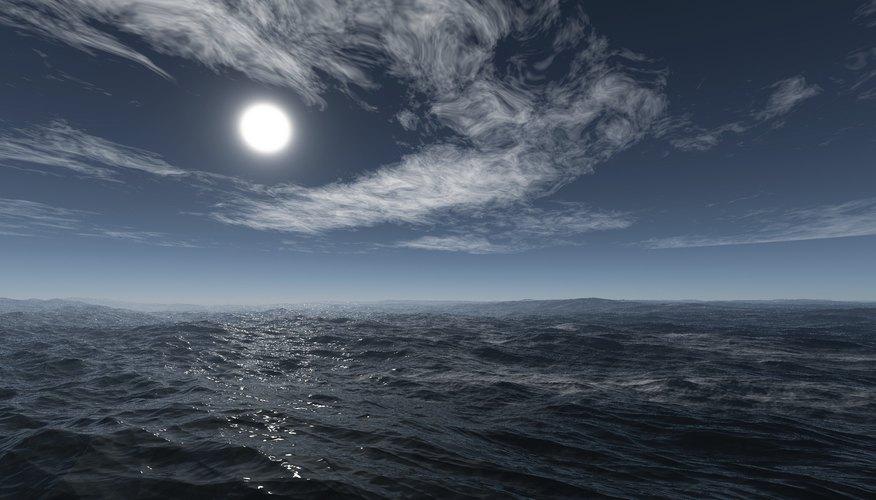 A moon rises over an ocean.