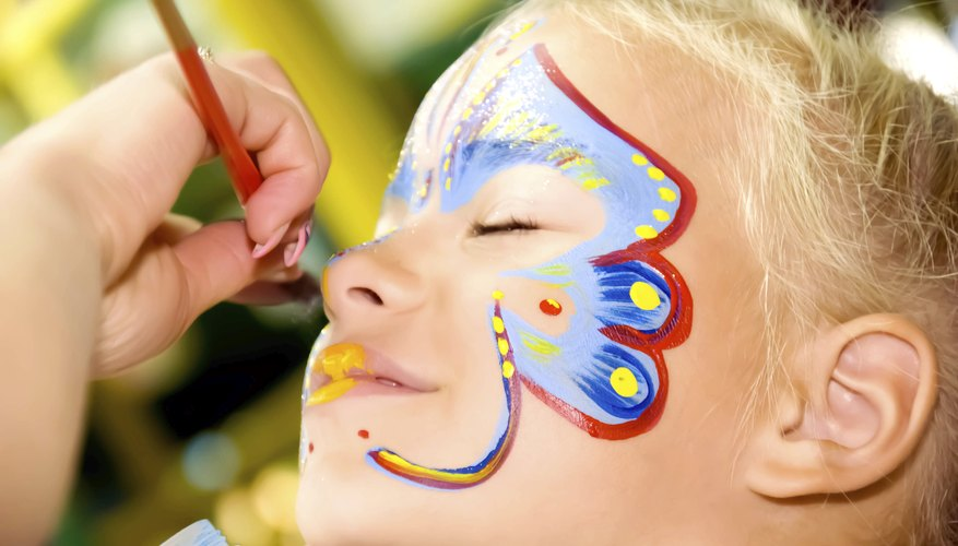 A young girl gets her face painted with a butterfly motif.
