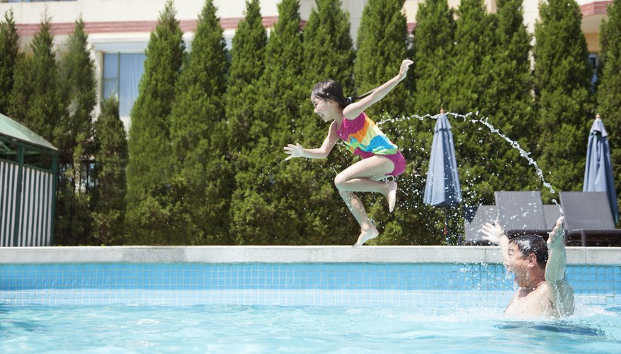 Girl jumping off of her dad's shoulders into a swimming pool.