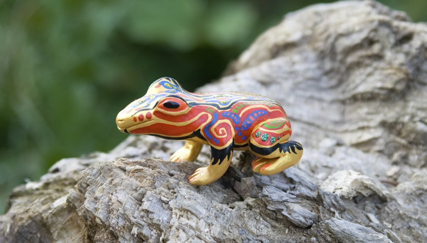 A painted clay frog sits on a log outside.
