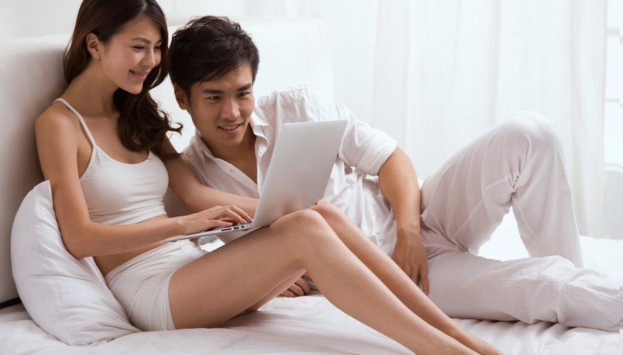A young couple is sitting in bed looking at a laptop.