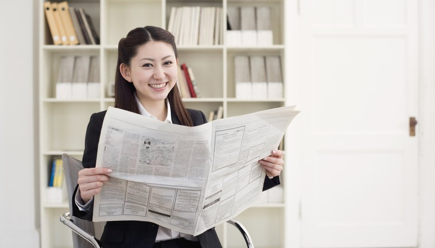 Portrait of young woman holding newspaper in office, smiling