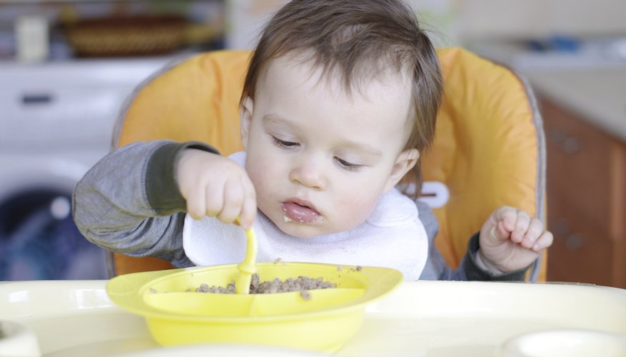 An infant boy eating some cereal.