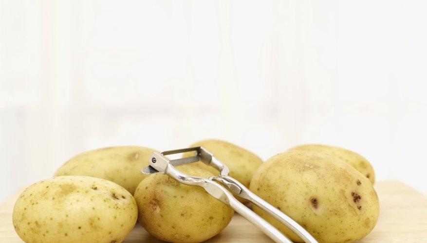 Small potatoes and peeler on cutting board.