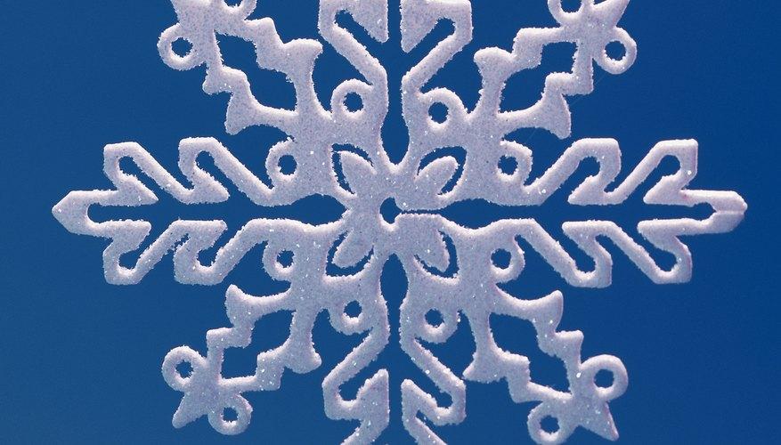 Recorta copos de nieve para ilustrar el concepto de los ejes de simetría.