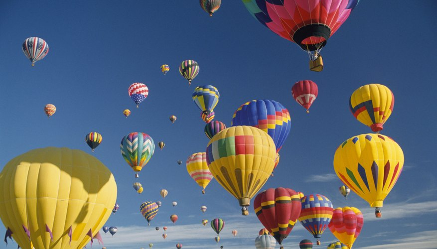 Hot air balloons illustrate how warm air expands and rises.
