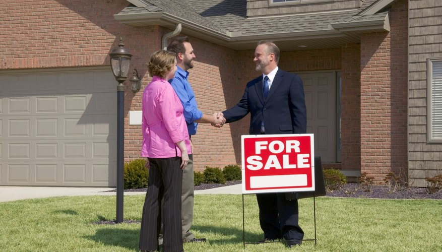 Businessman and couple shaking hands, For Sale sign on the lawn