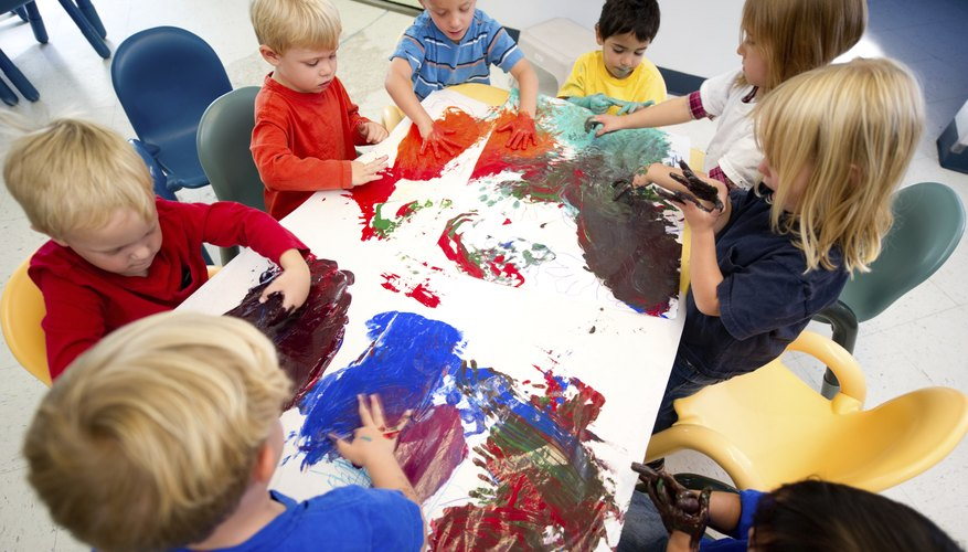 A group of young children fingerpaint