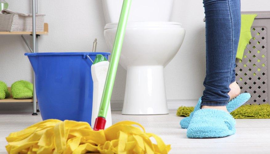A woman mops a bathroom floor.