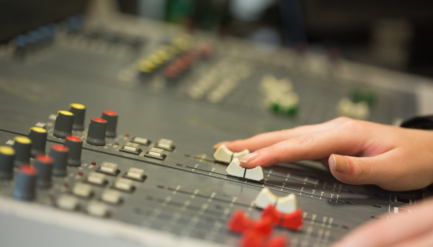 Hands working a mixing board
