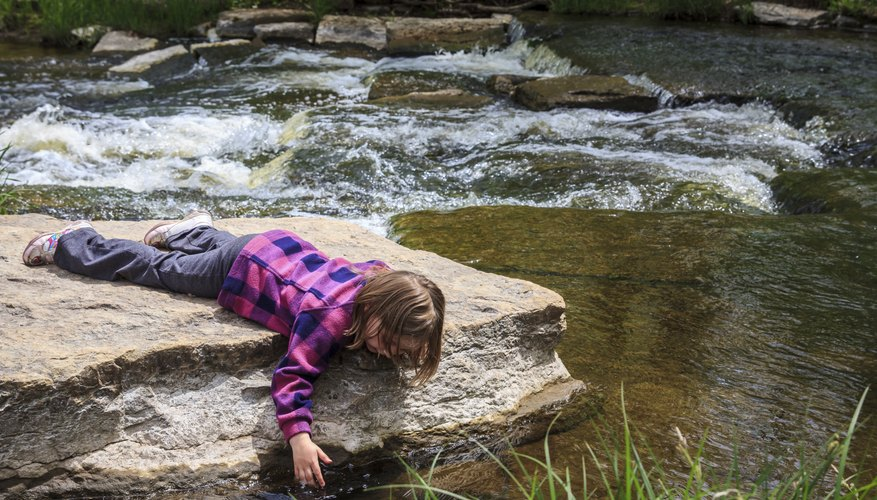 This young girl is studying a stream.