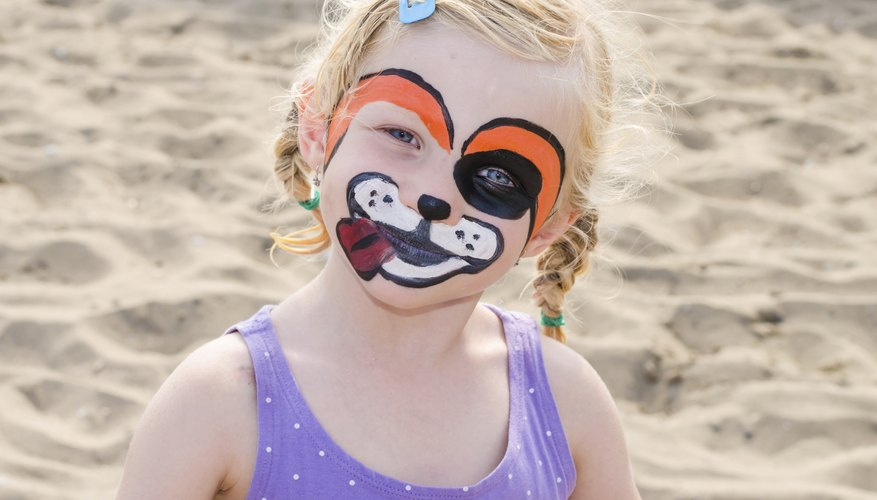 A girl with a painted face playing in the sand.