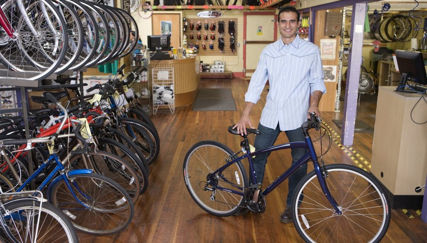 Proud business owner standing with bicycle in bike shop