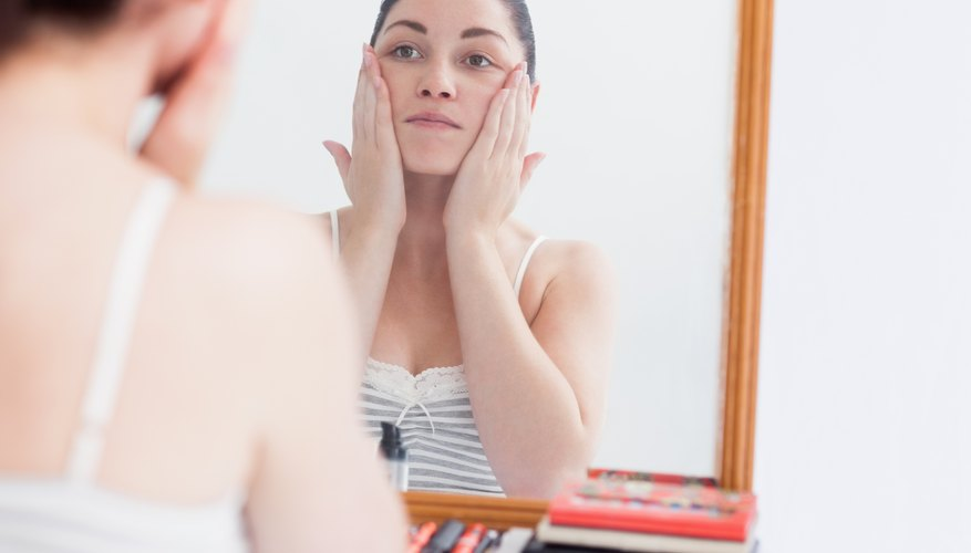 A woman applies moisturizer to her face.