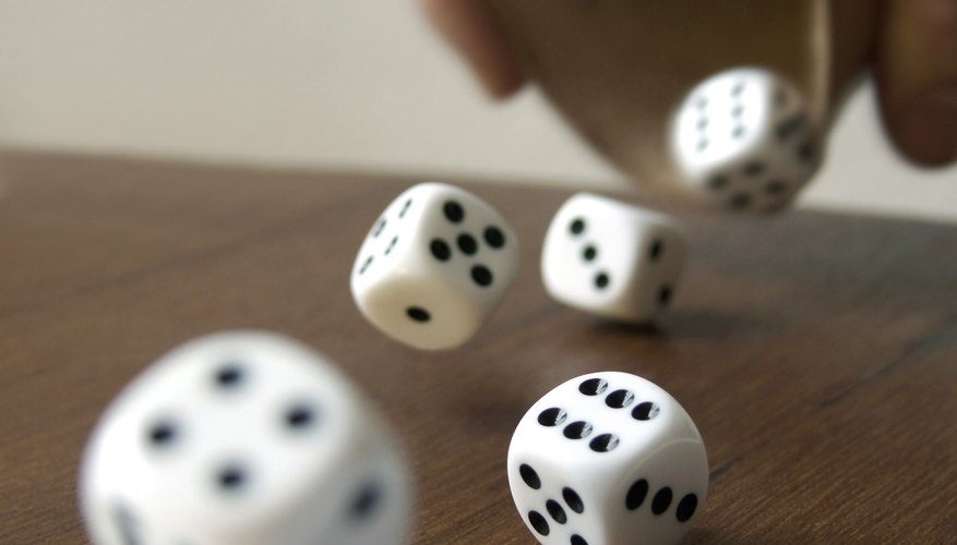 Dice rolling onto a table and out of frame.