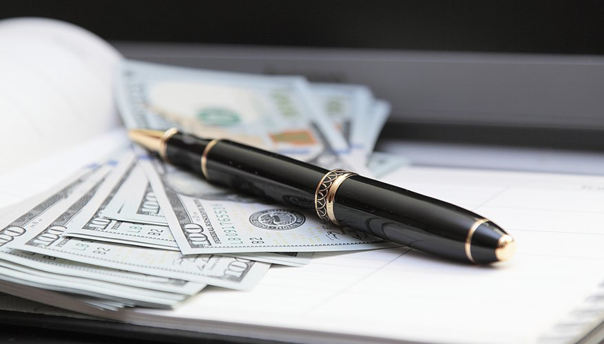 A close-up of an ink pen on top of bank notes.
