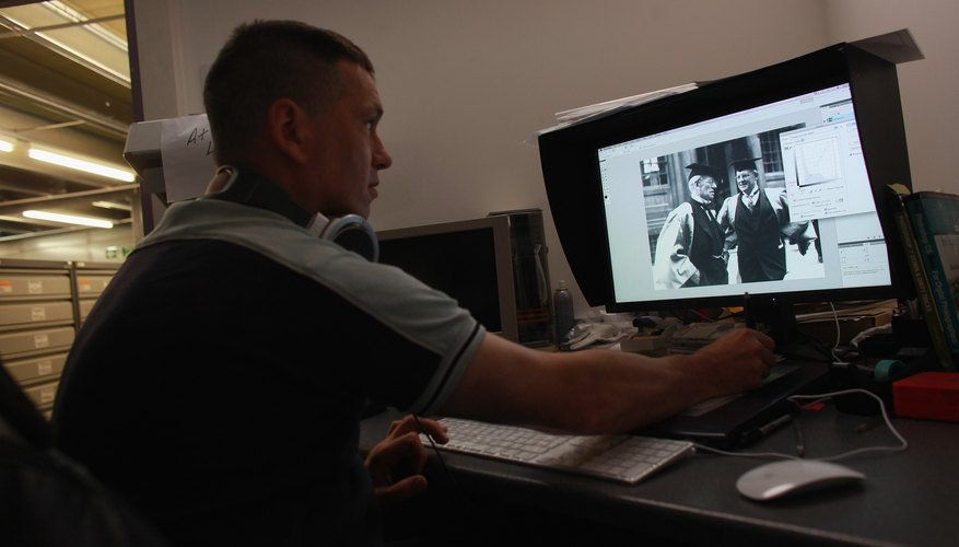 Retouching damaged photo at the Hulton photo archive in England.