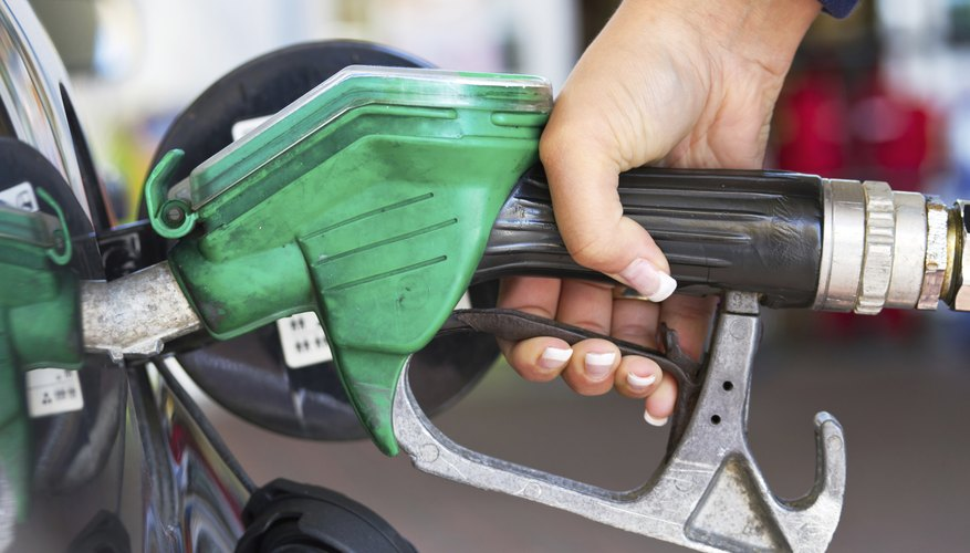 A woman refuels her car with gasoline.