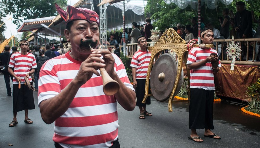 Flute player and gong on display during Bali festival