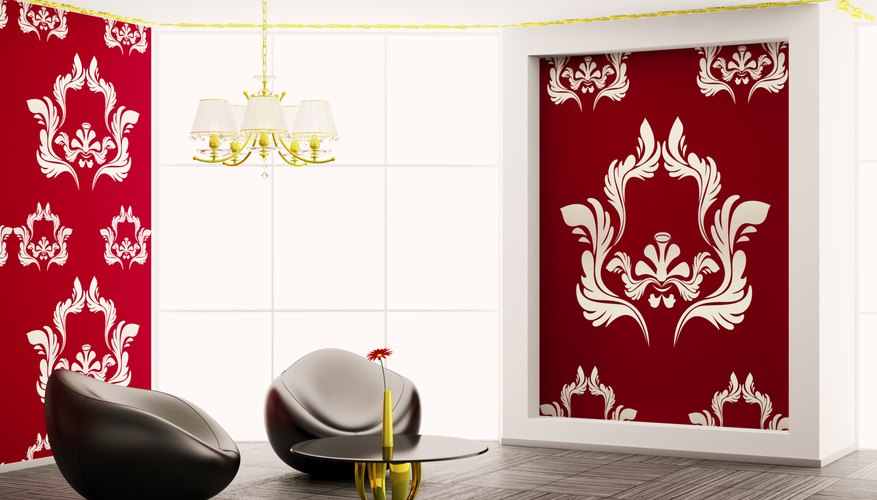A modern living room composed of leather chairs and white damask designs on red walls.