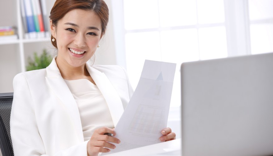 Young business lady holding paper in front of laptop