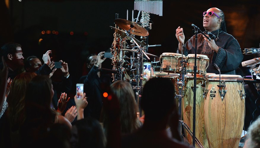 Stevie Wonder playing a variety of instruments in concert.