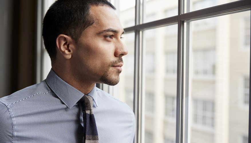 Young Hispanic business man looking out of window