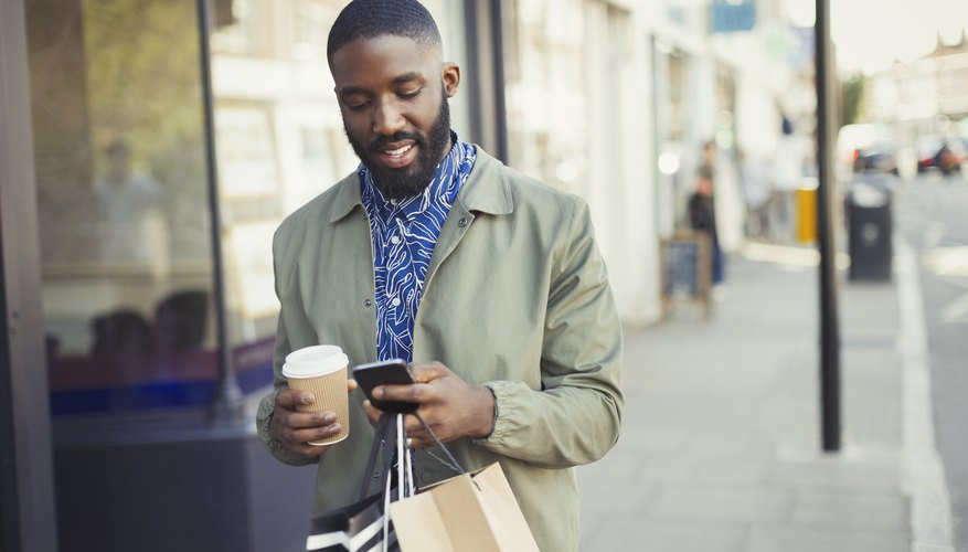 Young man with coffee and shopping bags texting with cell phone on urban sidewalk