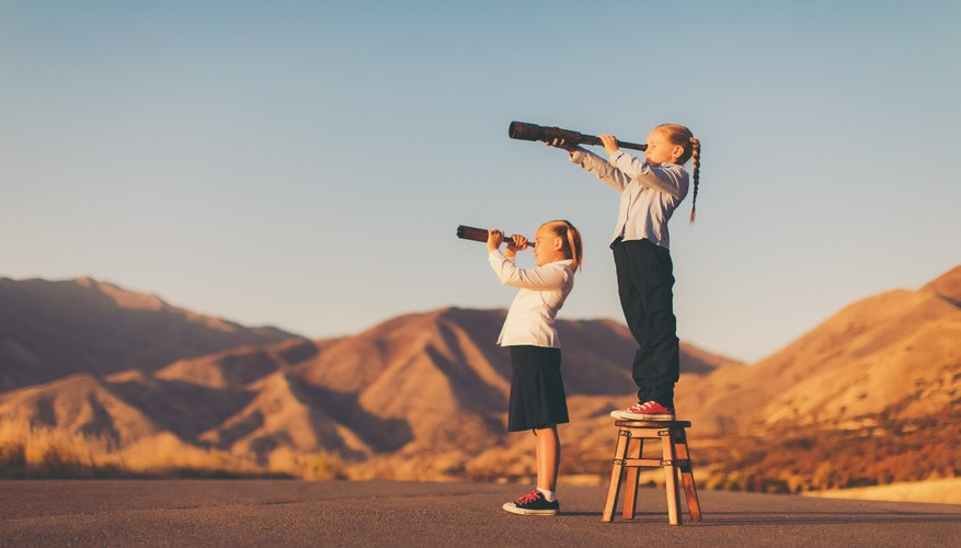Young Business Girl Looks through Telescope