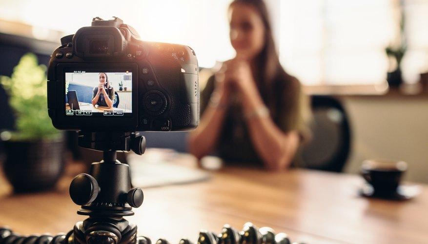 Digital camera on flexible tripod recording a video of woman at desk.