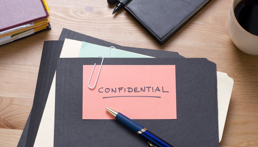 Black confidential files on a wooden desk with stationery
