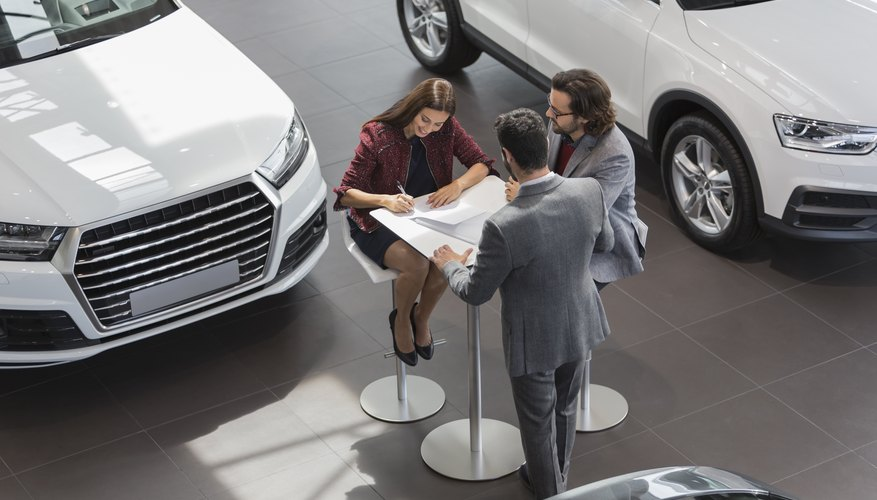 Car salesman watching couple customers signing financial contract paperwork in car dealership showroom