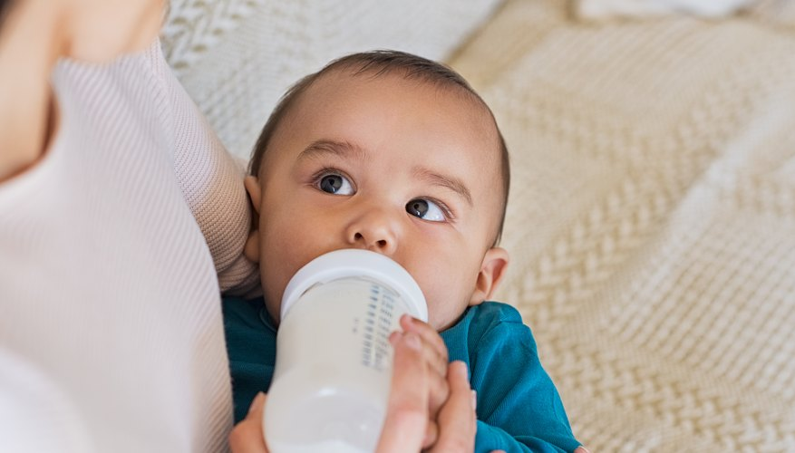 Baby looking at her mother while being fed with bottled milk