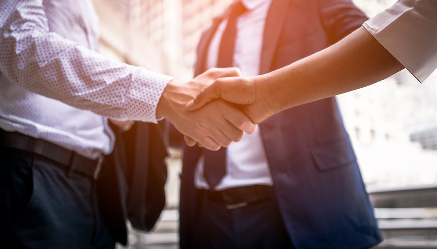 Business People Shaking Hands While Standing Outdoors