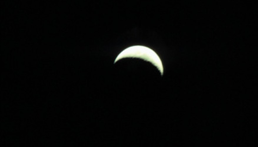 A sliver of the moon is visible in a crescent moon.