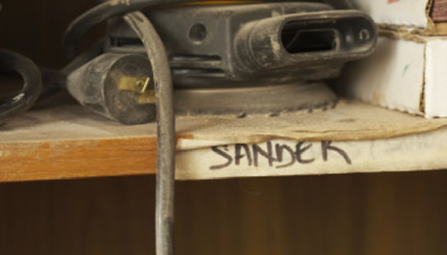 A power sander can help remove stubborn spots of paint on a concrete foundation.