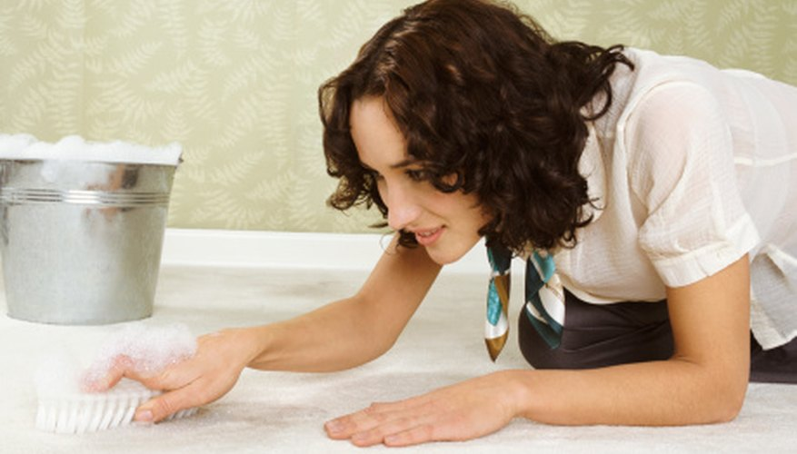 Using your scrubbing brush, apply the solution liberally to ensure it penetrates deep into the carpet fibers.