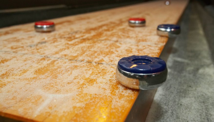 Indoor Shuffleboard Is Played On A Waxed Table, Which Pucks Slide On From  One End