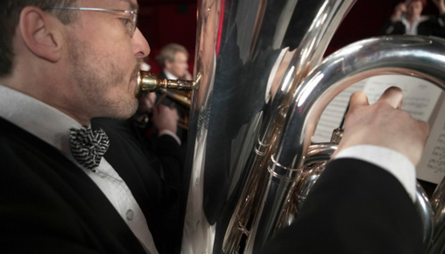 Brass instruments, such as the tuba, add extra volume to an orchestra performance.