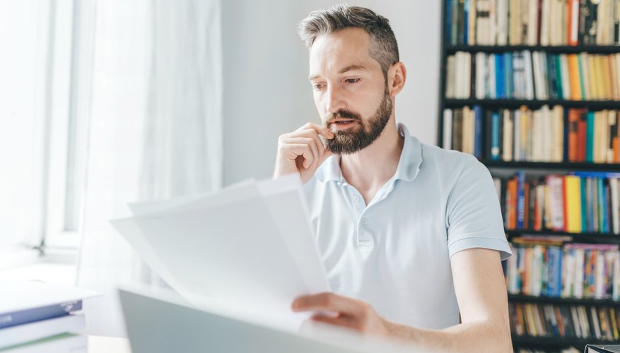 man with a beard looking over documents